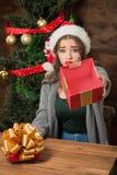 Beautiful girl demonstrating empty box of present near New Year tree Stock Photos