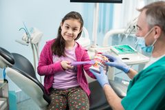 Girl in dentist chair educating proper tooth-brushing by her pediatric dentist, using dental jaw model and toothbrush. Beautiful girl in dentist chair educating royalty free stock photography