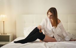 Beautiful girl in a depression in the white bedroom Royalty Free Stock Image
