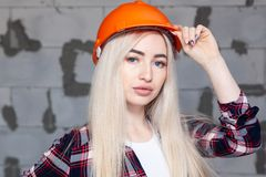 Beautiful girl the designer foreman blonde in an orange construction helmet and jeans overalls. Concept of repair in house,. Beautiful girl the designer foreman stock photography