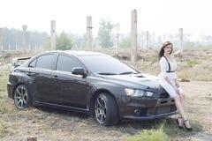 Beautiful girl detective near the sports car. Stock Photo