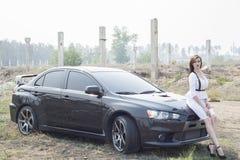 Beautiful girl detective near the sports car. Stock Photography