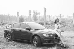 Beautiful girl detective near the sports car. Stock Photos