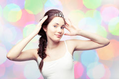 Beautiful girl in a diadem. Beautiful girl is putting on a diamond tiara and admiring herself, colorful pastel background Stock Image