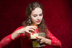 Beautiful girl dissatisfied with a small gift in a red dress. Royalty Free Stock Photos