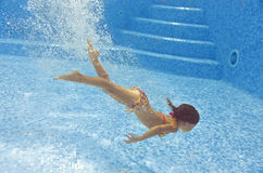 Beautiful girl dives and swims underwater in pool Royalty Free Stock Image