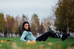 Beautiful girl does exercises with press at the grass Royalty Free Stock Photography