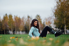 Beautiful girl does exercises with press at the grass Royalty Free Stock Images