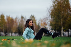 Beautiful girl does exercises with press at the grass Stock Photography