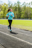 Beautiful girl does jogging in spring. Athletic girl goes in for sports in the open air Stock Images
