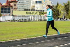Beautiful girl does jogging in spring. Athletic girl goes in for sports in the open air Stock Image