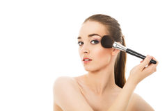 Beautiful girl does make-up with brush isolated. Beautiful girl does make-up with brush Royalty Free Stock Photography