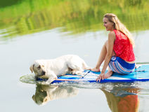 The beautiful girl and a dog in the boat. Royalty Free Stock Photography