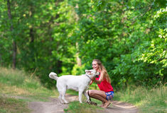 The beautiful girl and dog have sat down on a forest footpath Royalty Free Stock Photos