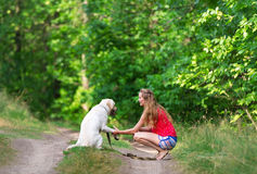 The beautiful girl and dog have sat down on a forest footpath Royalty Free Stock Photo
