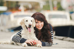 Beautiful girl with a dog on the pier in the summer Stock Photo