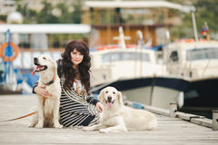 Beautiful girl with a dog on the pier in the summer Royalty Free Stock Images