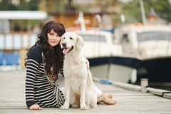 Beautiful girl with a dog on the pier in the summer Royalty Free Stock Photo
