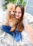 Beautiful girl with dog taken pictures of her self. Stock Photography
