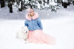Beautiful girl with a dog on a walk in the winter forest. beautiful girl and her pet stock photos