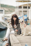 Beautiful girl with a dog on the waterfront Royalty Free Stock Photos