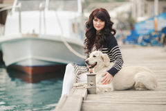 Beautiful girl with a dog on the waterfront Royalty Free Stock Image