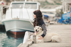 Beautiful girl with a dog on the waterfront Royalty Free Stock Photography