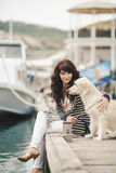 Beautiful girl with a dog on the waterfront Stock Photos