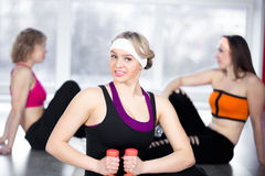 Beautiful girl doing fitness exercises with dumbbells in class Royalty Free Stock Photography