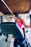 Beautiful girl doing fitness on treadmill or running machine. Beautiful girl doing fitness on treadmill and whipping her sweat Stock Photo