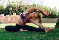 Beautiful girl doing flexibility exercise on the grass Stock Image