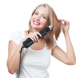 Beautiful girl doing hairstyle with hair brush Stock Photos
