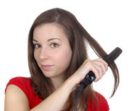 Beautiful girl doing hairstyle with hair iron Royalty Free Stock Photography