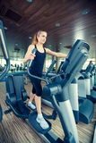 Beautiful girl doing indoor biking in a fitness Stock Photos