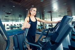 Beautiful girl doing indoor biking in a fitness. Club Royalty Free Stock Photos