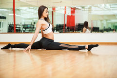 Beautiful girl doing a leg split at the gym Royalty Free Stock Photo