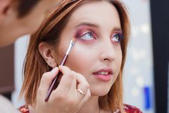 Beautiful girl doing make up, make up artist work stock photography