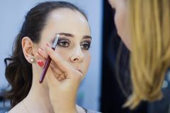 Beautiful girl doing make up, make up artist work stock images