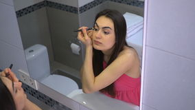 Beautiful girl doing makeup in bathroom and dyes her eyes with pencil stock video footage