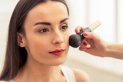 Beautiful girl doing makeup stock images
