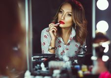 Beautiful girl doing makeup with red lipstick Royalty Free Stock Images