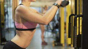 Beautiful girl doing pull-down exercise for upper body, reflection in mirror. Stock footage stock video footage