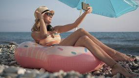 Beautiful girl doing selfie with smart phone on beach