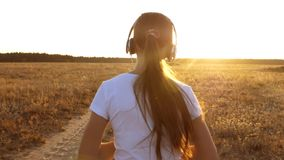 Beautiful girl doing sports exercises at sunset in countryside. girl in headphones runs along the road and listens to. Beautiful girl doing sports exercises at stock footage