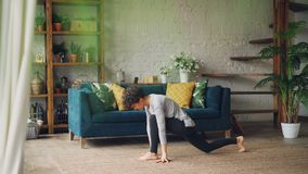 Beautiful girl is doing sports at home practising yoga asanas for health and beauty exercising on floor of apartment. Nice furniture, green plants and carpet stock footage