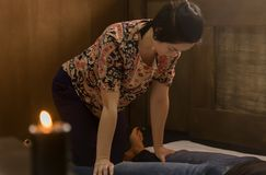 Beautiful girl doing thai back massage in spa saloon. Thai massage or Thai yoga massage treatment.  Stock Images