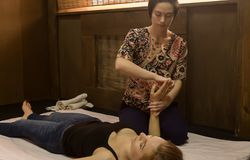 Beautiful girl doing thai back massage in spa saloon. Thai massage or Thai yoga massage treatment Stock Photo