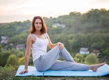 Beautiful girl doing yoga exercise in twisting. Outdoors Royalty Free Stock Photography