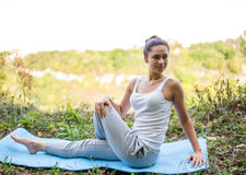 Beautiful girl doing yoga exercises on the carpet in nature Royalty Free Stock Photo
