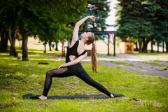 Beautiful girl doing yoga on green grass in park at summer morning Stock Photos